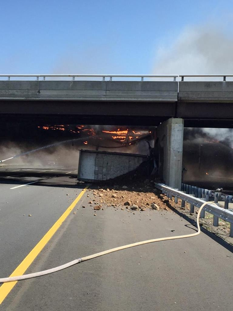 A fire burns around a dump truck on Tuesday after it hit an overpass and overturned on the New Jersey Turnpike. (Sgt. Jeremy Micewicz, New Jersey State Police via AP)