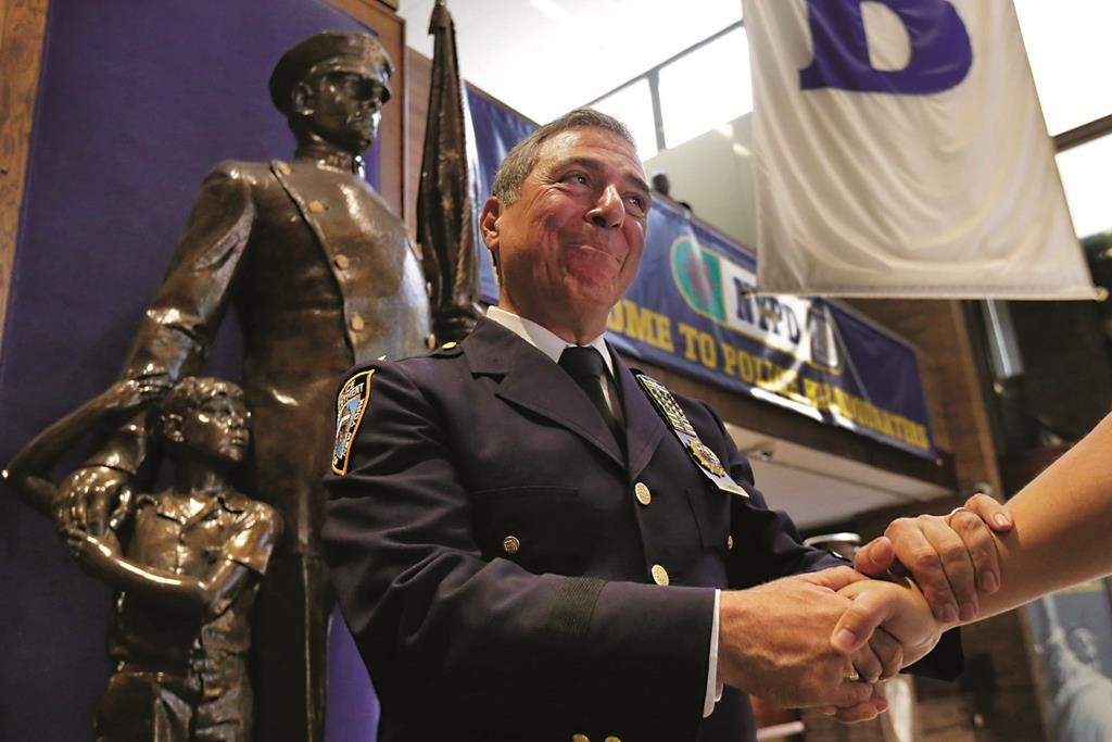 Lt. John Cambria, the NYPD's top hostage negotiator, who is retiring after more than three decades, on Friday receives a congratulatory handshake at Police Headquarters. (AP Photo/Richard Drew)