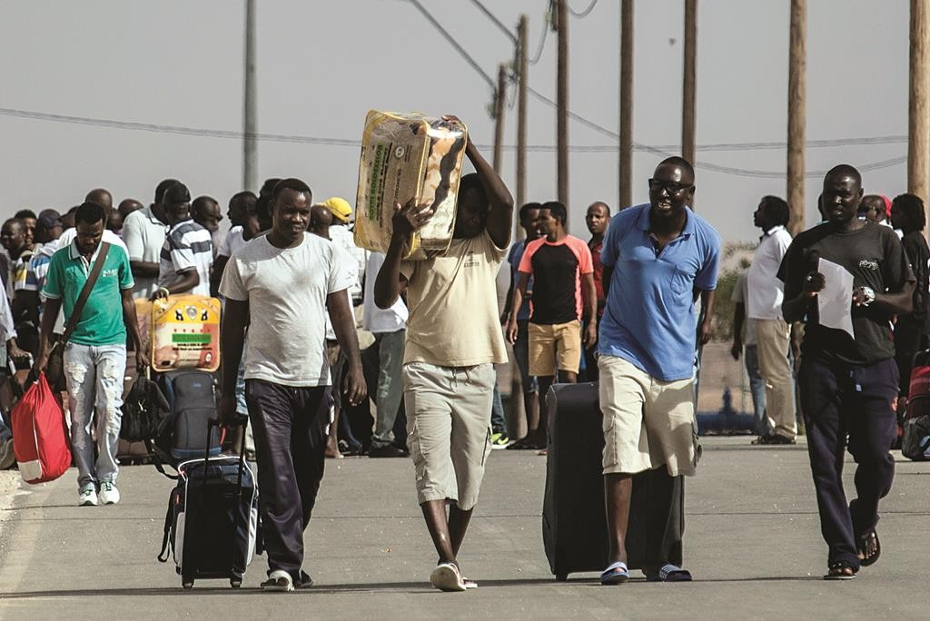 African illegal migrants walking out of the Holot detention center in the Negev on Tuesday, after the High Court ordered their release. (AP Photo/Tsafrir Abayov)