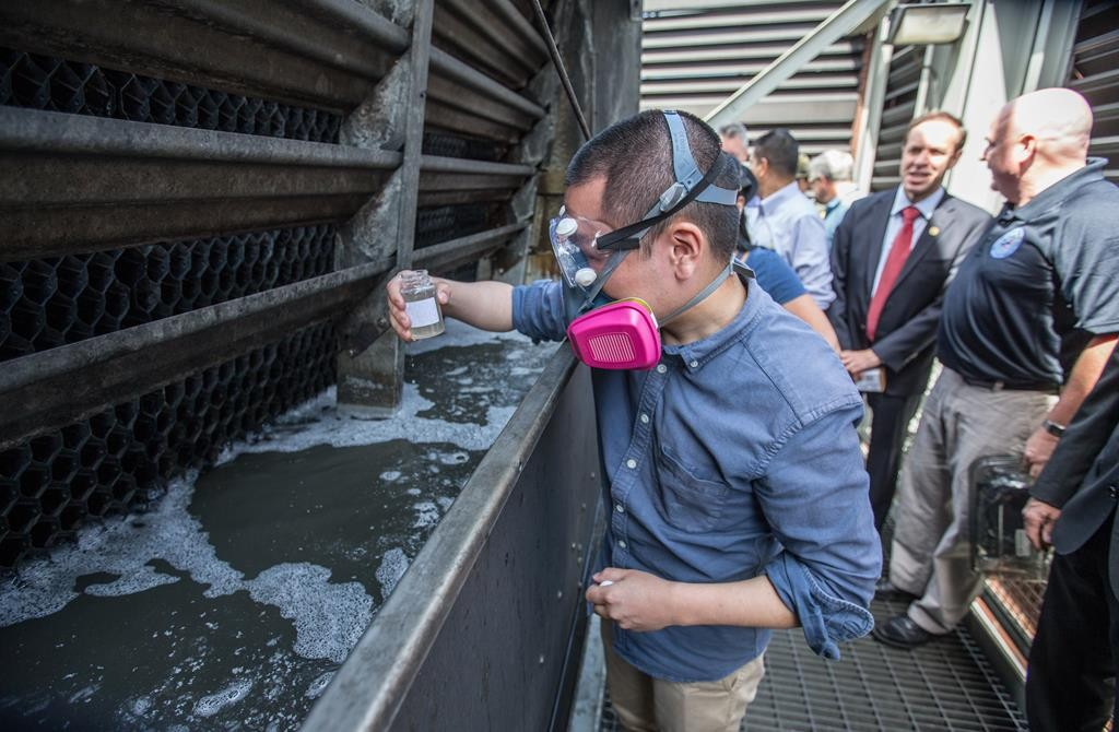 A state environmental official on Saturday takes a water sample from a cooling tower on the roof of Montefiore Medical Center in the Bronx. (Office of Gov. Cuomo)