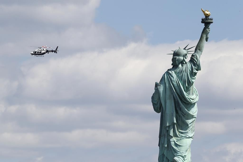 An NYPD helicopter circles over the Statue of Liberty on April 24, after Liberty Island was evacuated due to a bomb threat. Jason Paul Smith was arrested Wednesday for it. (AP Photo/Julio Cortez)