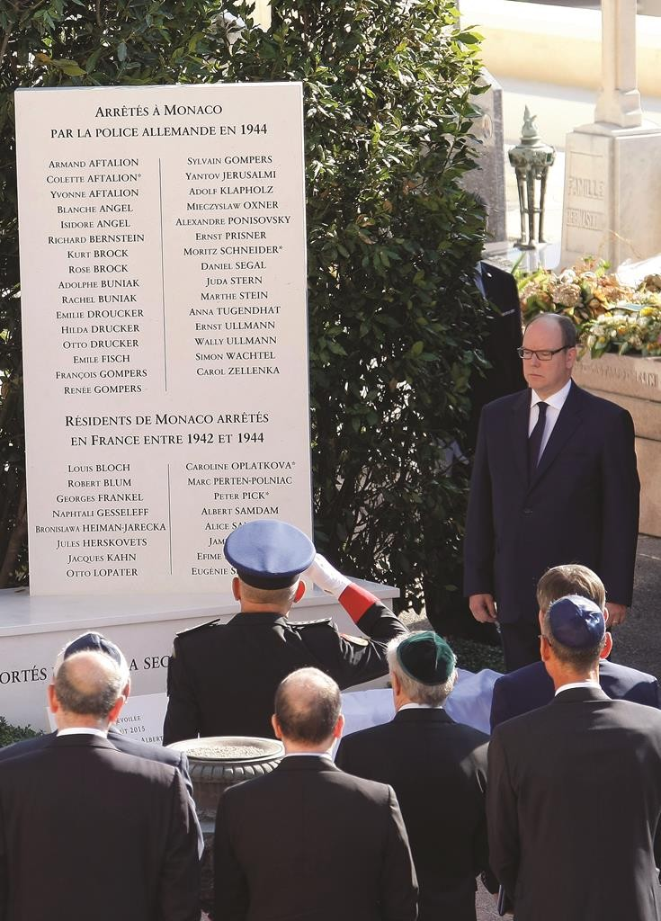 Prince Albert II (R) pays his respects after unveiling a monument to Jews deported from the Riviera principality during World War II in a cemetery in Monaco, Thursday, Aug. 27, 2015. (AP Photo/Claude Paris)
