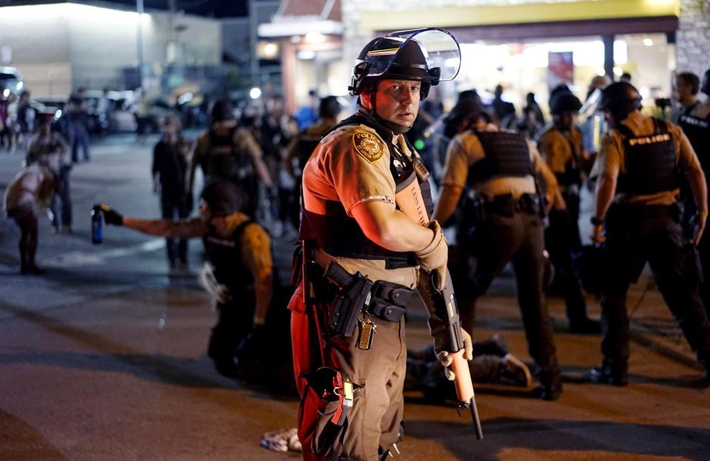 A police officer holds his weapon as a suspect is detained (rear) in Ferguson, Mo., Monday. (Reuters/Rick Wilking)