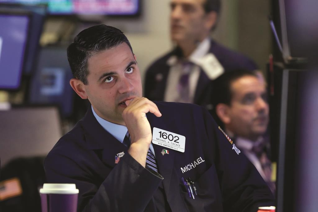 Specialist Michael Cacace works on the floor of the New York Stock Exchange, Tuesday. (AP Photo/Richard Drew)