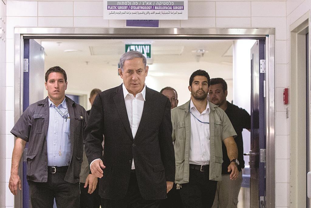 Flanked by his security detail, Israeli Prime Minister Binyamin Netanyahu seen at Hadassah Ein Kerem Medical Center in Yerushalayim on Tuesday, where he visited firebombing victim Inbar Azrak. (Yonatan Sindel/Flash90)