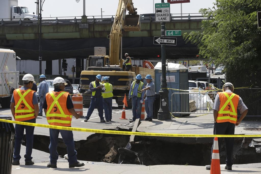 Construction crews on Tuesday work at the site of a sinkhole on 5th Avenue and 64th Street in Sunset Park, Brooklyn. (AP Photo/Mary Altaffer)