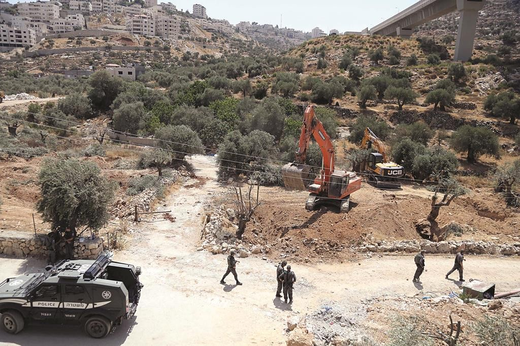Israeli soldiers stand guard as an Israeli excavator uproots olive trees to make way for Israel's separation barrier, in the West Bank town of Beit Jala near the Jewish neighborhood of Gilo and the Palestinian town of Bethlehem on August 17, 2015. Photo by Flash90 *** Local Caption *** çééì ùåèø ùåèøéí áðéä çåîä áéú â'àìä âéìä ùîéøä ãçôåø âãø ääôøãä
