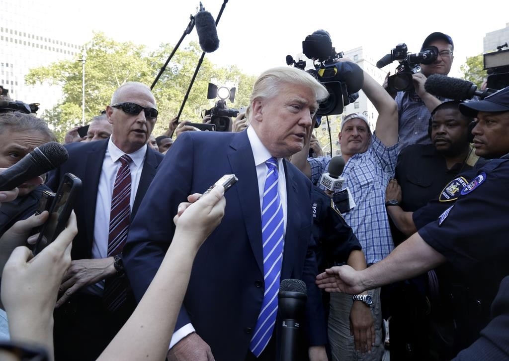 Republican presidential candidate Donald Trump is surrounded by media as he arrives Monday for jury duty in Manhattan. (AP Photo/Richard Drew)