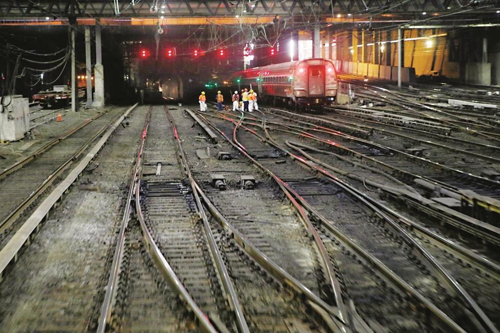 Workers on Monday stand near an outbound train on the tracks under Penn Station. (AP Photo/Mel Evans)