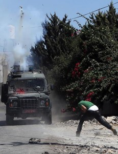 A Palestinian protester throws stones at a vehicle of Israeli security forces firing tear- gas canisters during clashes in the village of Kafr Qaddum, near Shechem, on Friday. (JAAFAR ASHTIYEH/AFP/Getty Images)
