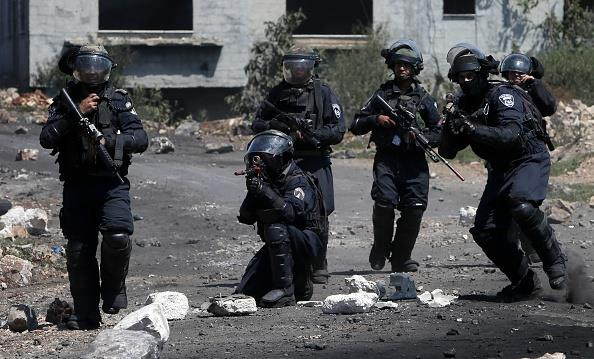 Members of Israeli security forces aim their weapons at Palestinian stone throwers during clashes in the village of Kafr Qaddum, near Shechem, on Friday. (JAAFAR ASHTIYEH/AFP/Getty Images)