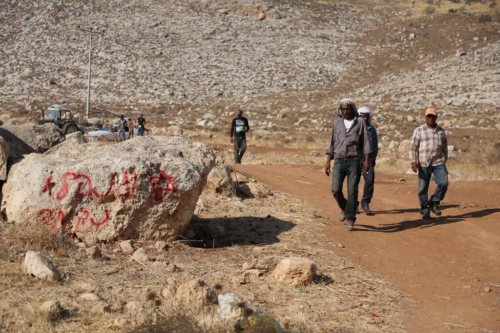 Bedouin residents standing near 'price tag' graffiti that was allegedly written by arsonists, on Thursday.  (Flash90)