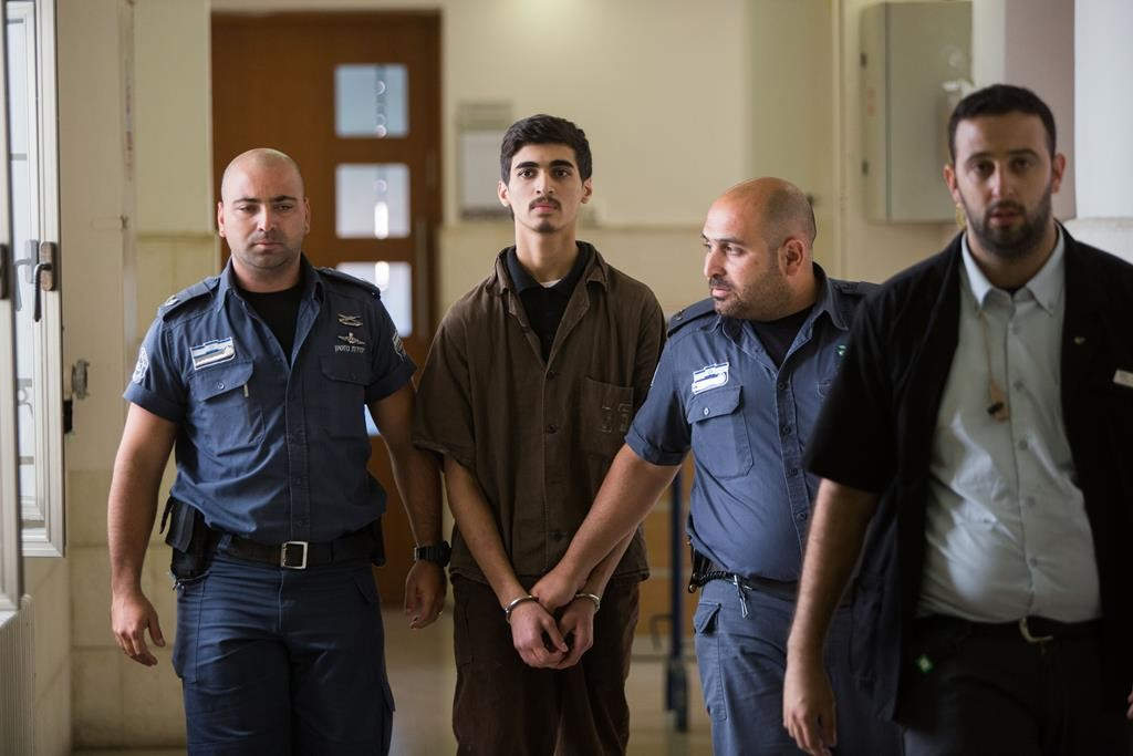 Fares Sharitah, 19, of the Beit Hanina neighborhood of eastern Yerushalayim is brought to the courtroom of the Yerushalayim District Court on Thursday, being charged with attempting to join and be active in ISIS. (Yonatan Sindel/Flash90)