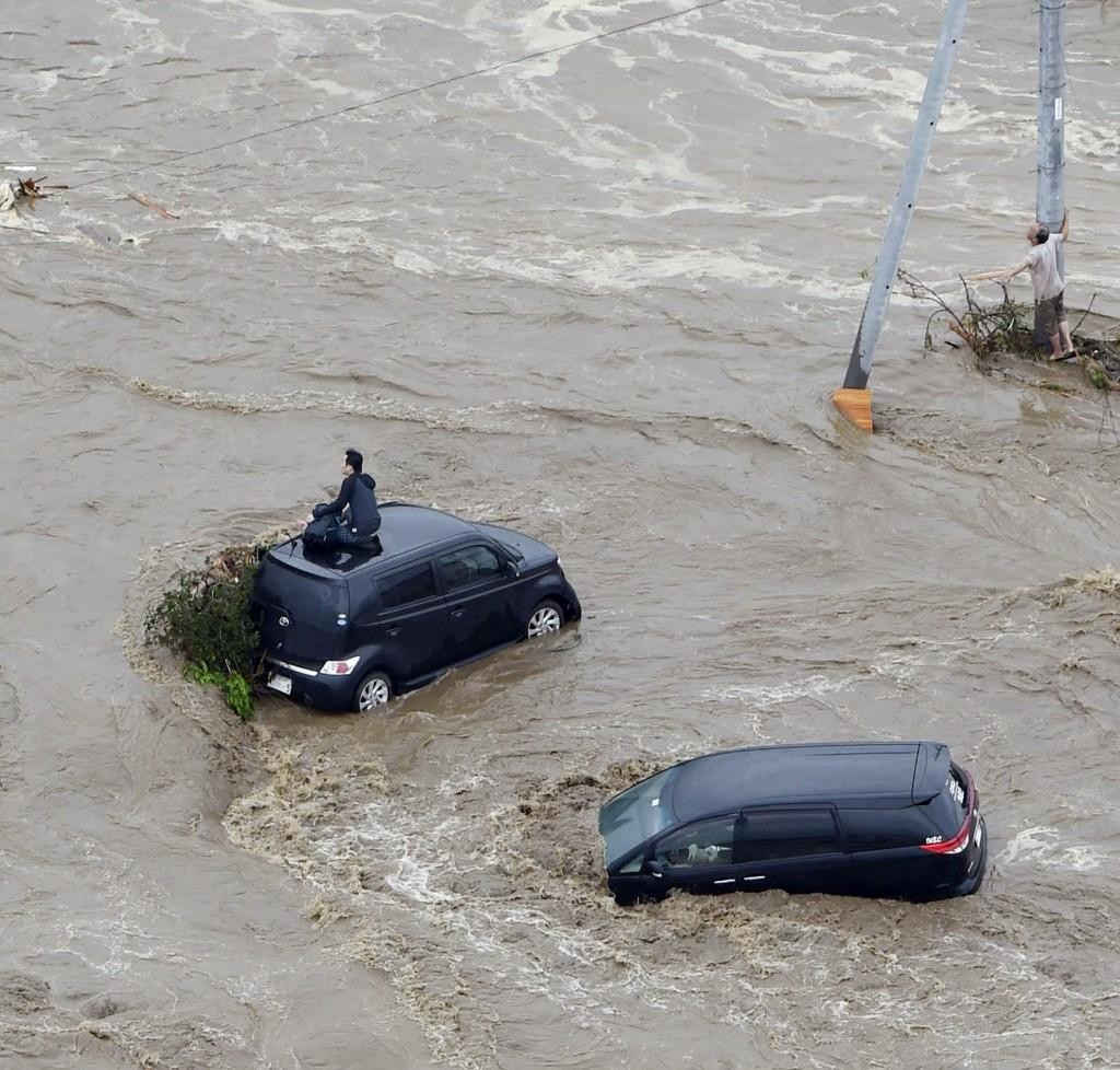 People wait for help in a flooded street in Joso, Ibaraki prefecture, northeast of Tokyo, on Thursday.  (Kyodo News via AP)