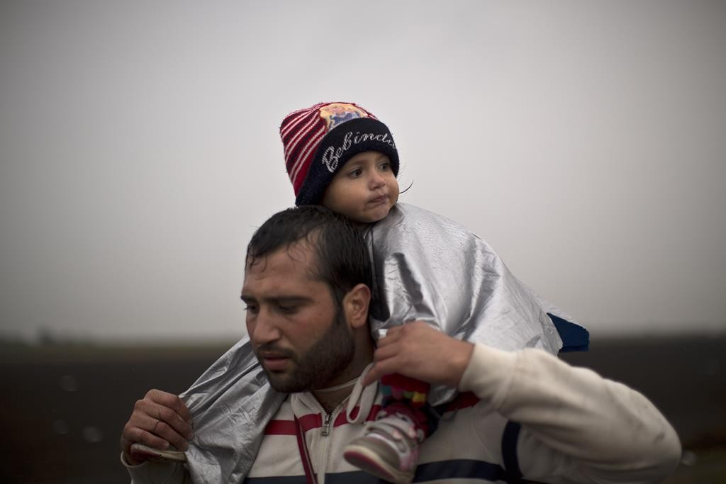 A man carrying his child on his shoulder, walks on a railway toward a makeshift camp for asylum seekers in Roszke, southern Hungary, Thursday. (AP Photo/Muhammed Muheisen)