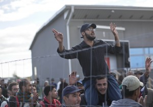 People sing and dance as they wait in line in order to board buses organized by the Austrian government in Hegyeshalom, Hungary, Sunday. The Austrian authorities organized a free bus service for migrants and refugees that reach the Hungarian border town of Hegyeshalom, with the buses transporting people to the Austrian border with Germany. (AP Photo/Marko Drobnjakovic)
