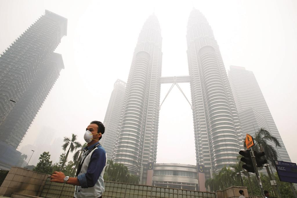 A masked man runs across the street in front of Petronas Twin Towers, shrouded by haze, in Kuala Lumpur, Malaysia, on Monday, Sept. 14, 2015.  (AP Photo/Joshua Paul)
