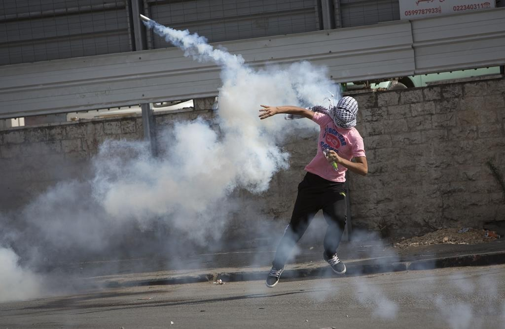 A Palestinian throws back a tear gas canister at Israeli soldiers during disturbances at Har HaBayis on Tuesday. (AP Photo/Majdi Mohammed)