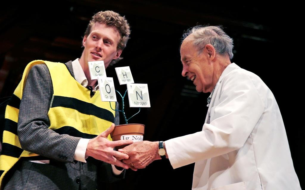 Michael Smith, left, on Thursday accepts his trophy from Dudley Herschbach, the 1986 Nobel Laureate in Chemistry, at the Ig Nobel Prize ceremony at Harvard University. (AP Photo/Charles Krupa)
