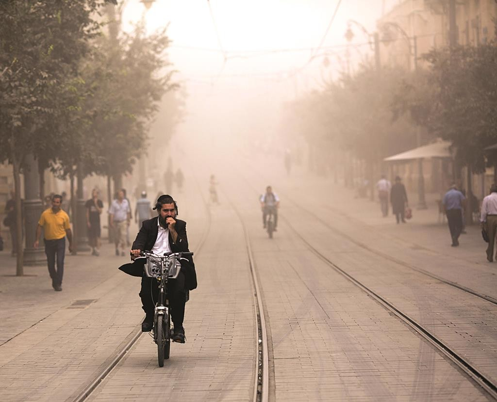 Riding out the sandstorm along the Light Rail tracks on Jaffa Road in Yerushalayim on Tuesday. (Yonatan Sindel/Flash90)
