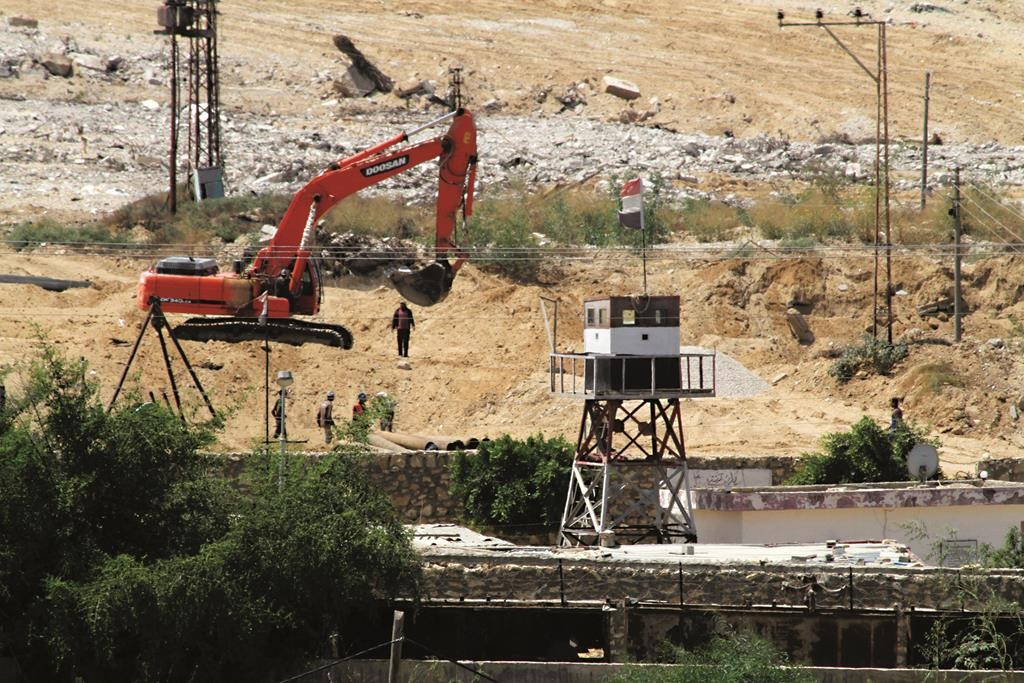 Bulldozers and workers on the Egyptian side of the border with town of Rafah in the southern Gaza Strip this week.  (Abed Rahim Khatib /Flash90)