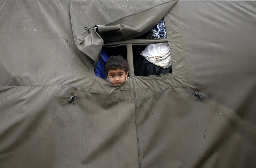 A child looks out from a tent at a migrant camp in Opatovac, Croatia Monday . (REUTERS/Dado Ruvic)