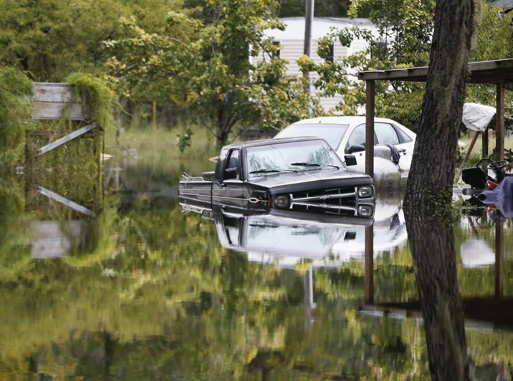 Floodwater surrounds cars parked behind a home in Ridgeville, S.C., on Tuesday. Despite an improving forecast, it will still take weeks for the state to return to normal after being pummeled by a historic rainstorm.  (AP Photo/John Bazemore)