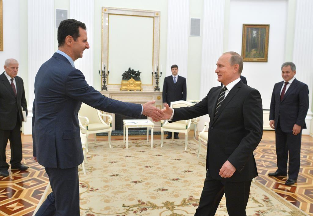 In this photo taken on Tuesday, Russian President Vladimir Putin, right, shakes hand with Syrian President Bashar Assad in the Kremlin in Moscow, Russia.  (Alexei Druzhinin, RIA-Novosti, Kremlin Pool Photo via AP)