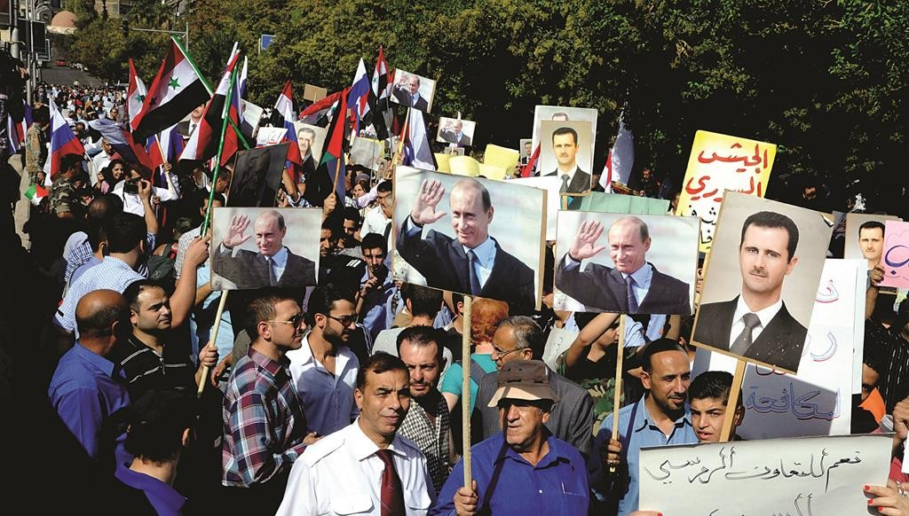 This photo released by the Syrian official news agency SANA, shows Syrians holding photos of Syrian President Bashar Assad and Russian President Vladimir Putin, during a rally to thank Moscow for its intervention in Syria, in front of the Russian embassy in Damascus, Syria, Tuesday. (SANA via AP)