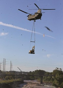 A South Carolina National Guard Chinook helicopter delivers a large piece of excavating equipment to help fill a breach in a canal in Columbia, S.C., Tuesday. (AP Photo/Chuck Burton)