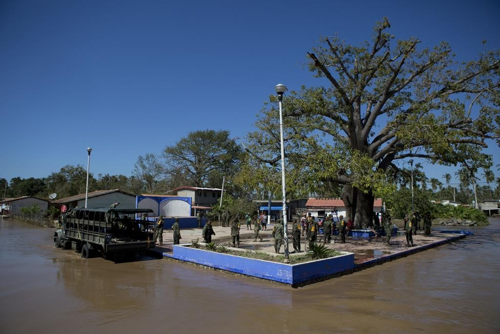 Soldiers arrive to check on village residents staying dry on a raised village plaza surrounded by receding flood waters, two days after the passage of Hurricane Patricia, in the village of Rebalse, Mexico, Sunday.  (AP Photo/Rebecca Blackwell)