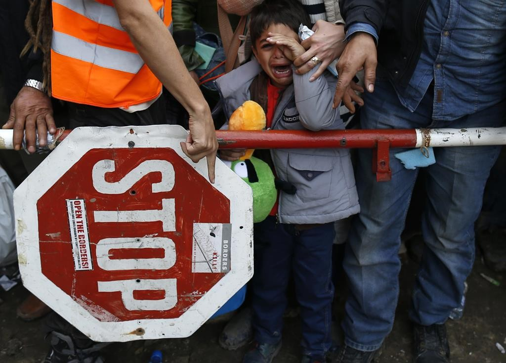 A child cries as a volunteer (L) gives instructions to a migrant family at a border line between Serbia and Croatia, on Sunday. (AP Photo/Darko Vojinovic)