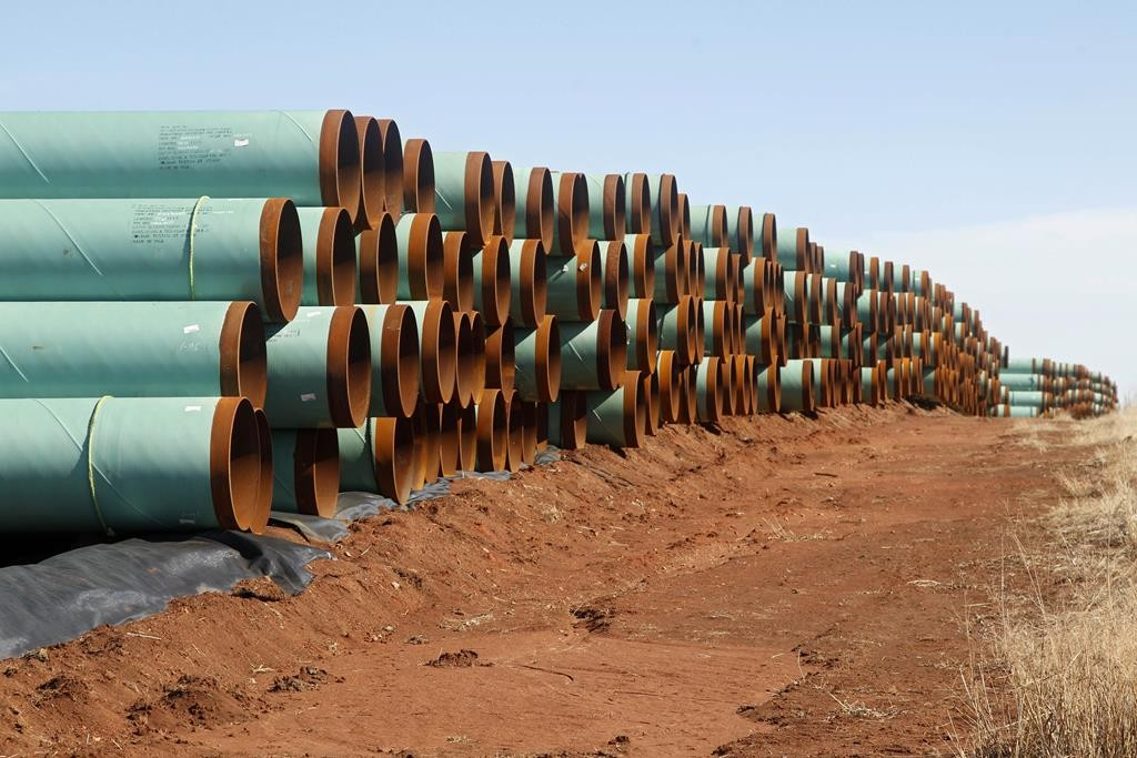 In this Feb. 1, 2012 file photo, miles of pipe for the stalled Canada-to-Texas Keystone XL pipeline are stacked in a field near Ripley, Okla.  (AP Photo/Sue Ogrocki, File)