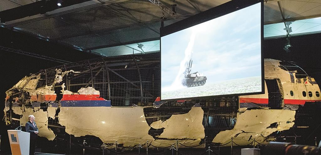 A video shows the launch of a BUK missile, while a part of the reconstructed forward section of the fuselage is displayed behind, as Tjibbe Joustra, left, head of the Dutch Safety Board, presents the board's final report into what caused Malaysia Airlines Flight 17 to break up high over Eastern Ukraine last year, during a press conference in Gilze-Rijen, central Netherlands, Tuesday. (AP Photo/Peter Dejong)