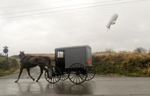 An unmanned Army surveillance blimp which broke loose from its ground tether in Maryland floats through the air about 1,000 feet about the ground while dragging a several thousand foot tether line just south of Millville, Pa., Wednesday. (Jimmy May/Bloomsburg Press Enterprise via AP)