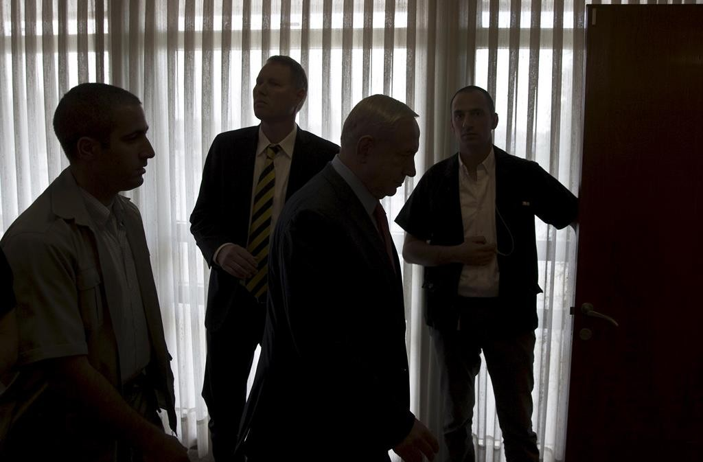 Israeli Prime Minister Binyamin Netanyahu (2nd R) is silhouetted as he leaves after delivering a statement to the media at the Knesset, following a visit by Arab-Israeli MK Basel Ghattas on Wednesday to Har HaBayis. (REUTERS/Ronen Zvulun)