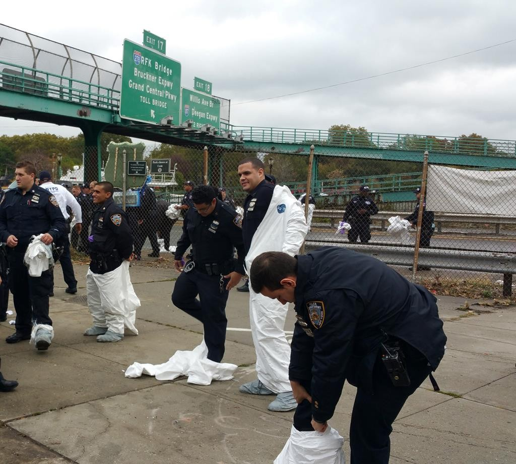 NYPD officers remove white suits worn to protect against contaminating evidence Sunday during a ground search near the scene where a gun was recovered from the Harlem River. (AP Photo/Verena Dobnik)