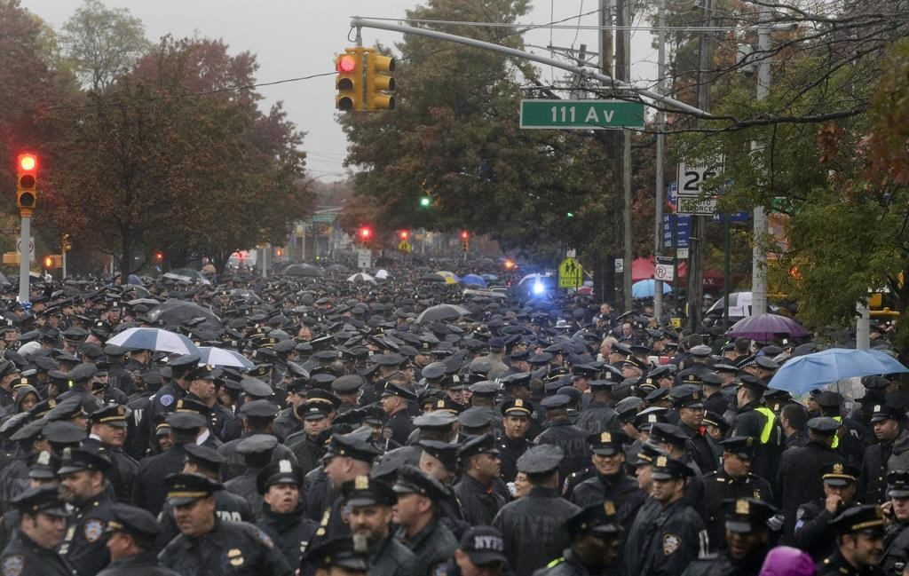 Hundreds of New York police officers gather Wednesday on a Queens street for the funeral of Officer Randolph. (AP Photo/Julie Jacobson)
