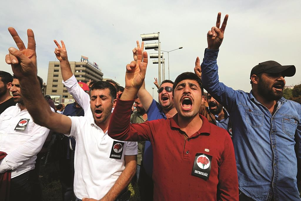 Protesters flash the V-sign and chant slogans as they protest Saturday's bombing attacks, during a rally in Ankara, Turkey, Sunday. (AP Photo/Burhan Ozbilici)