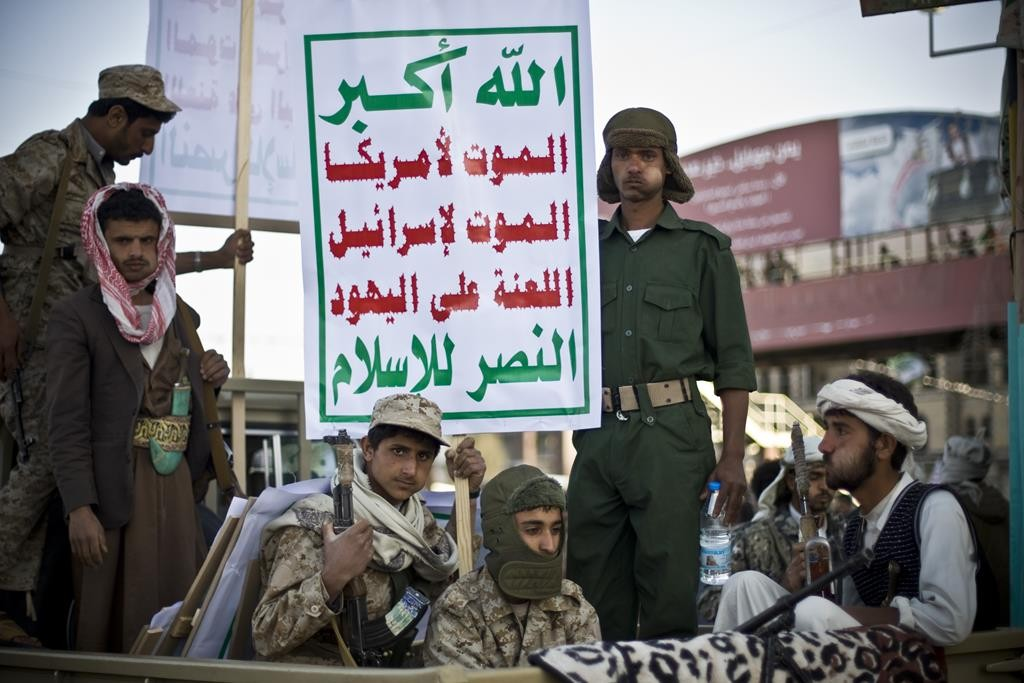 """Houthi Shiite fighters guard a street during a demonstration to show support for their comrades in Sanaa, Yemen, Friday, Jan. 23, 2015. Arabic slogans on the posters reads, """"Death to America. Death to Israel. A curse on the Jews. Victory to Islam.""""  (AP Photo/Hani Mohammed)"""