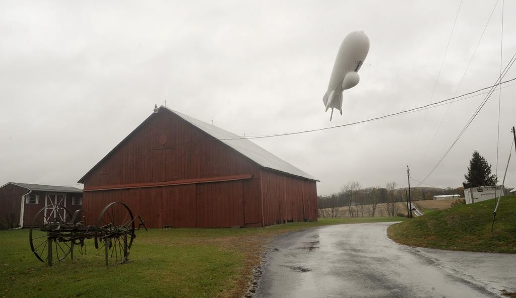 An unmanned Army surveillance blimp floats through the air while dragging a tether line south of Millville, Pa., Wednesday. (Jimmy May/Bloomsburg Press Enterprise via AP)