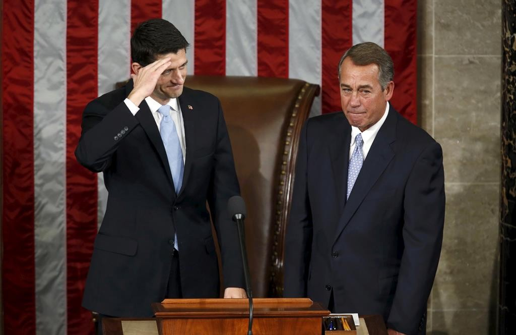 U.S. House of Representives Speaker-elect Paul Ryan (L) salutes the members of the House as he stands with outgoing Speaker John Boehner after Ryan was elected in Washington, Thursday.  (REUTERS/Gary Cameron)