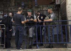 "An Israeli border policeman checks papers at the entrance to the Old City in Yerushalayim on Sunday, Hoshana Rabbah. Israeli police barred Palestinians from the Old City on Sunday in response to stabbing attacks that killed two Israelis, Hy""d, and wounded three others. (AP Photo/Mahmoud Illean)"