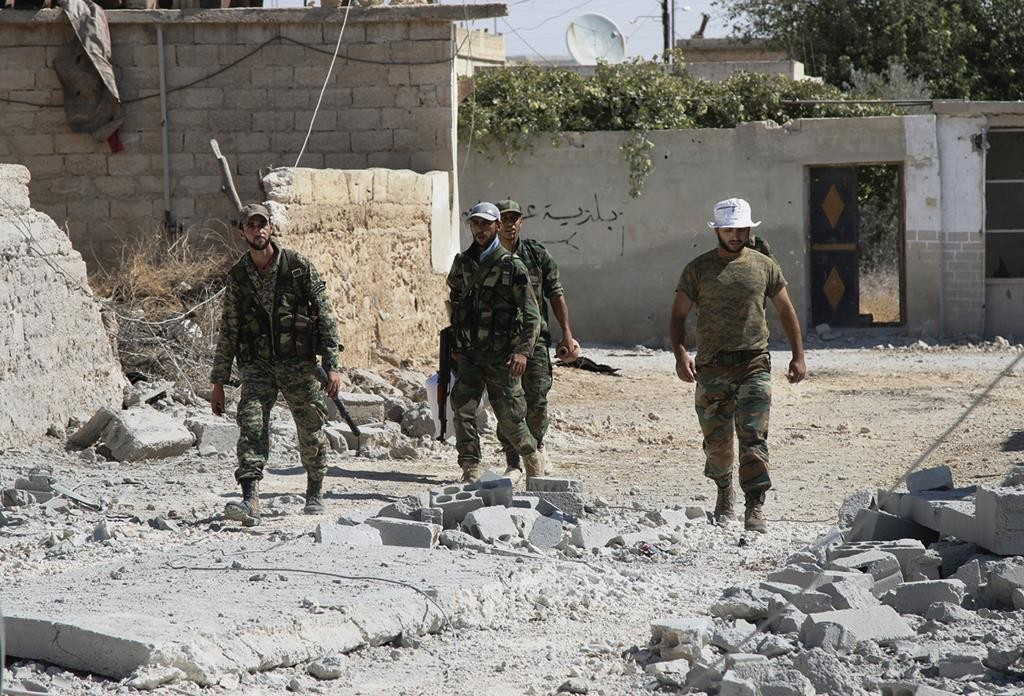 Syrian army soldiers walk in Achan, Hama province, Syria. Russian jets intensified their airstrikes Monday in the central Syrian province as government and allied troops pushed out insurgents from local villages to expand their control of the area, activists and a military statement said.  (Alexander Kots/Komsomolskaya Pravda via AP)