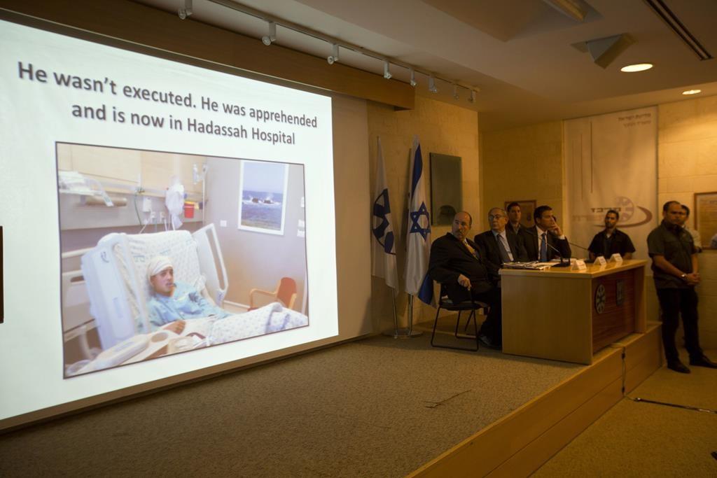Israeli Prime Minister Benjamin Netanyahu, second left, watches the screen during a press conference at the Foreign Ministry in Yerushalayim. The conference was held to expose untruths and inaccuracies in media reporting about Palestinian violence in Israel, Thursday, Oct. 15, 2015. (AP Photo/Sebastian Scheiner)
