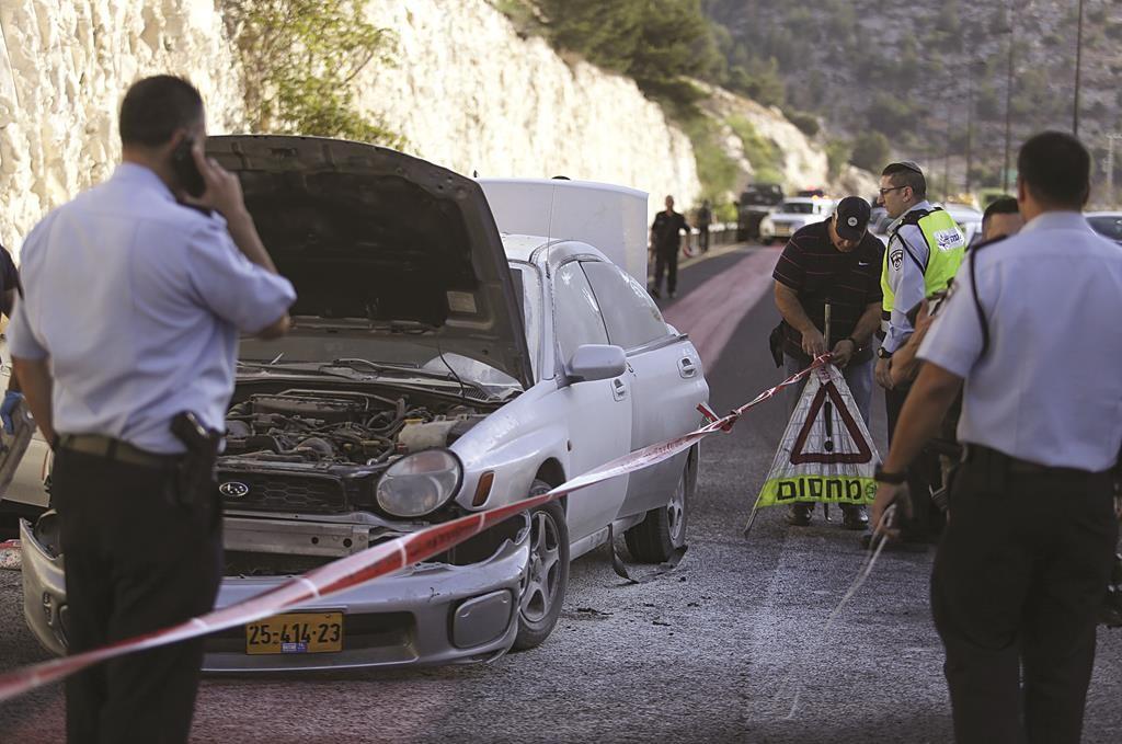 Israeli police seen by a vehicle damaged from a terror bombing near Maalei Adumim on Sunday. (REUTERS/Noam Moskovitz)