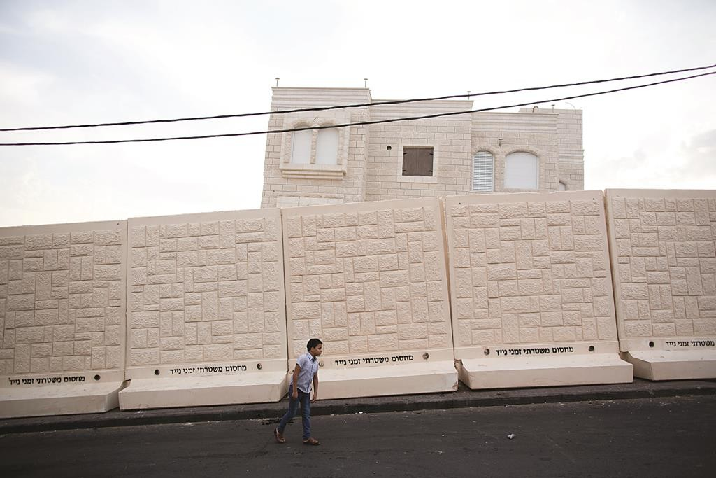A Palestinian boy seen in front of newly placed concrete walls in the eastern Yerushalayim neighborhood of Jabel Mukaber, where Molotov cocktails have been thrown almost nightly at Jewish homes across the road. (Yonatan Sindel/Flash90)