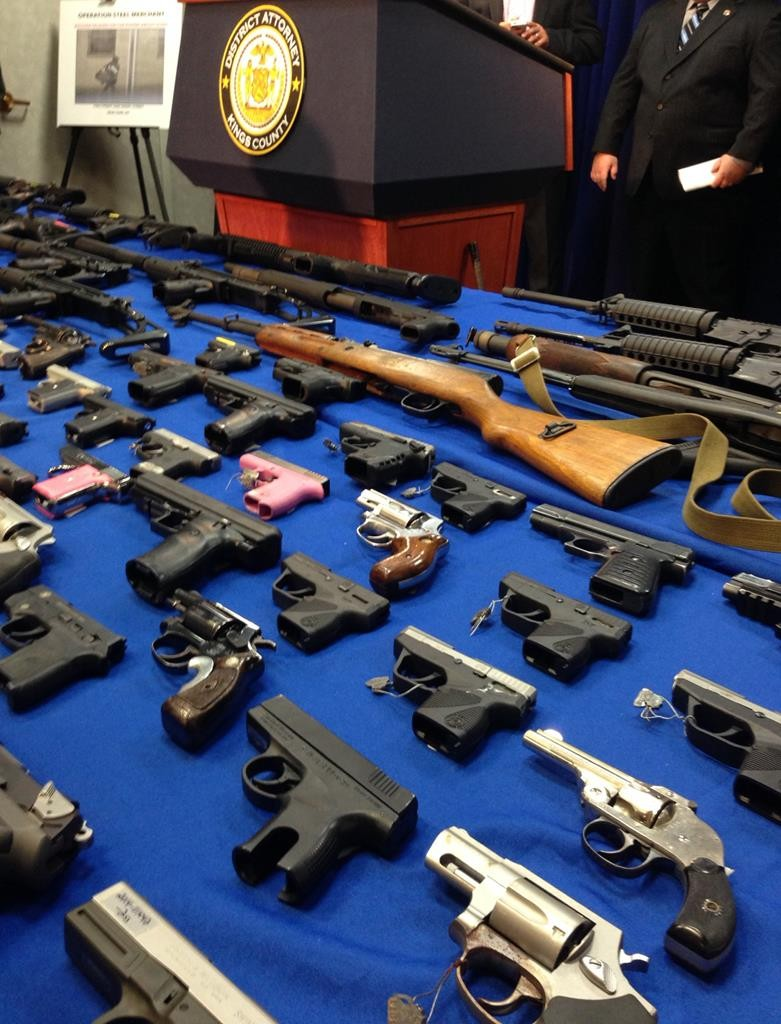 Weapons rest on a table Wednesday at the Brooklyn District Attorney's office. (AP Photo/Tom Haya)