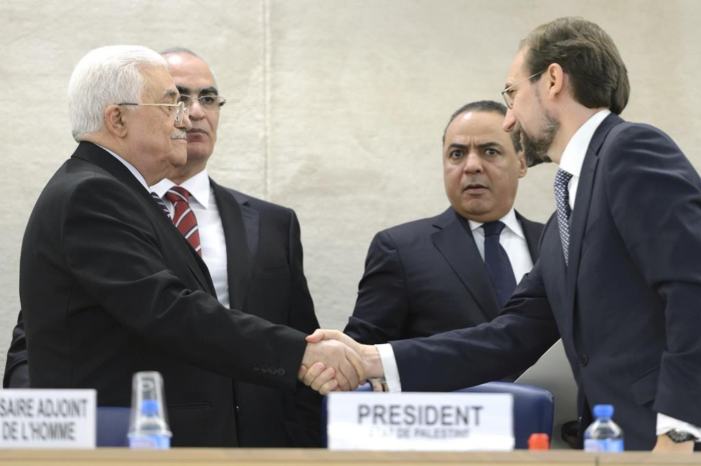 Pelestinian Authority President Mahmoud Abbas (L) shakes hands with Zeid Ra'ad Al Hussein, right, United Nations High Commissioner for Human Rights, during a meeting at the European headquarters of the United Nations, in Geneva, Switzerland, Wednesday. (Martial Trezzini/Keystone via AP)