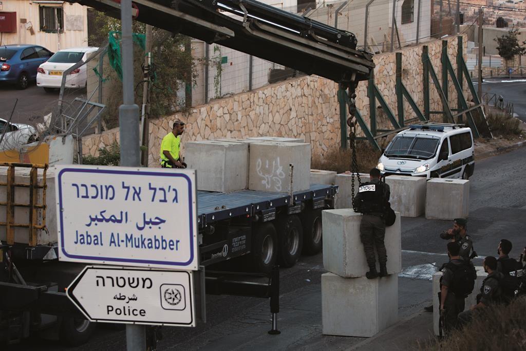 Israeli Border policemen setting up a road block at the entrance to the eastern Yerushalayim neighborhood of Jabel Mukaber on Wednesday. (Yonatan Sindel/Flash90)